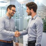 Two smiling business men shaking hands together after successful meeting.